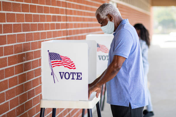 Senior Black Man Voting with a Mask A senior black man casts his ballot on election day. election stock pictures, royalty-free photos & images