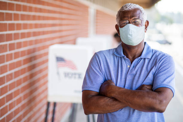 Senior Black Man Voting with a Mask stock photo