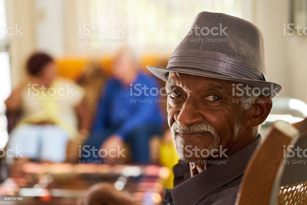 Senior Black Man With Hat Looking At Camera In Hospice stock photo