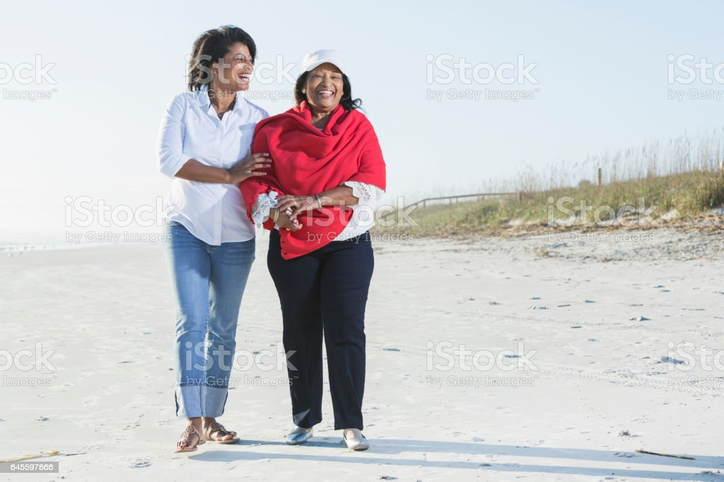 senior black woman and adult daughter walking on beach stock photo