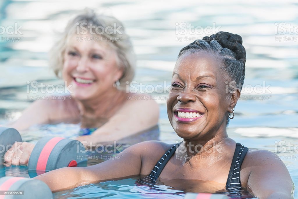 Senior black woman and friend doing water aerobics stock photo