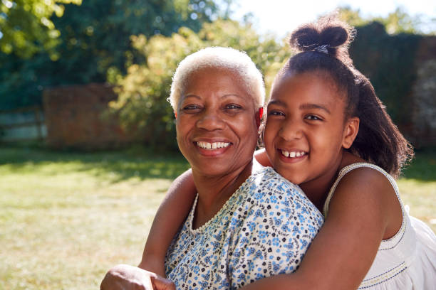 Senior black woman and granddaughter sit embracing outside stock photo