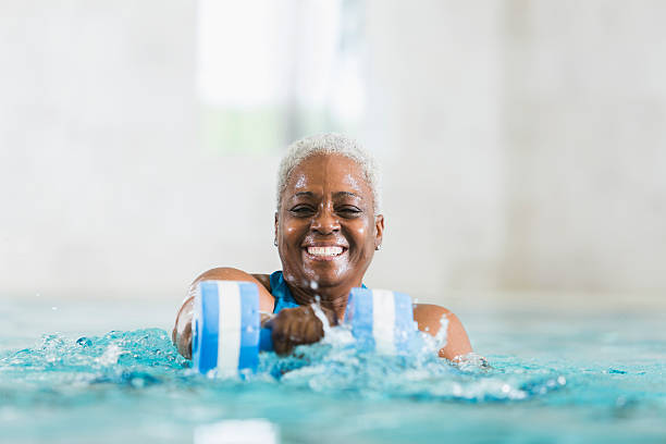 senior black woman exercising, doing water aerobics - aerobics stock photos and pictures