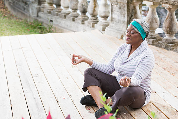 Senior black woman in yoga lotus pose Portrait of a senior African American woman meditating, in yoga lotus pose.  She is sitting on a deck by the water, legs crossed, with her eyes closed and a peaceful expression on her face. lotus position stock pictures, royalty-free photos & images