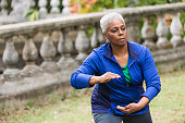 A senior African American woman in the park, practicing Tai Chi.  She has a serious expression on her face as she concentrates on her pose.  She is wearing a royal blue jacket over a green shirt and gray leggings.