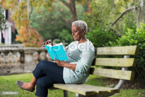 A senior African American woman in the park, sitting on a bench reading a book.