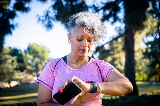 A beautiful black woman running with a fitness tracker.
