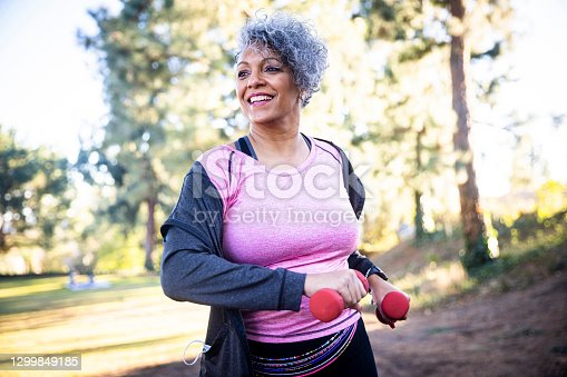 istock Senior Black Woman Stretching and Exercising with Weights 1299849185