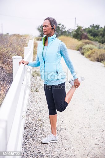 A beautiful senior black woman stretching and getting ready to work out