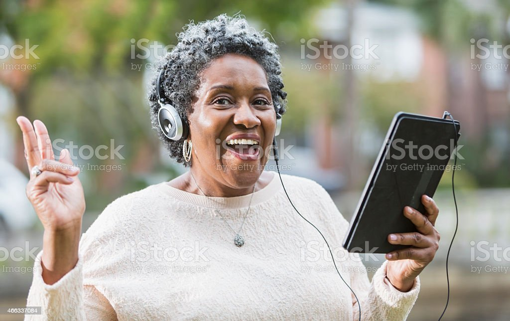 Senior black woman using digital tablet, singing stock photo