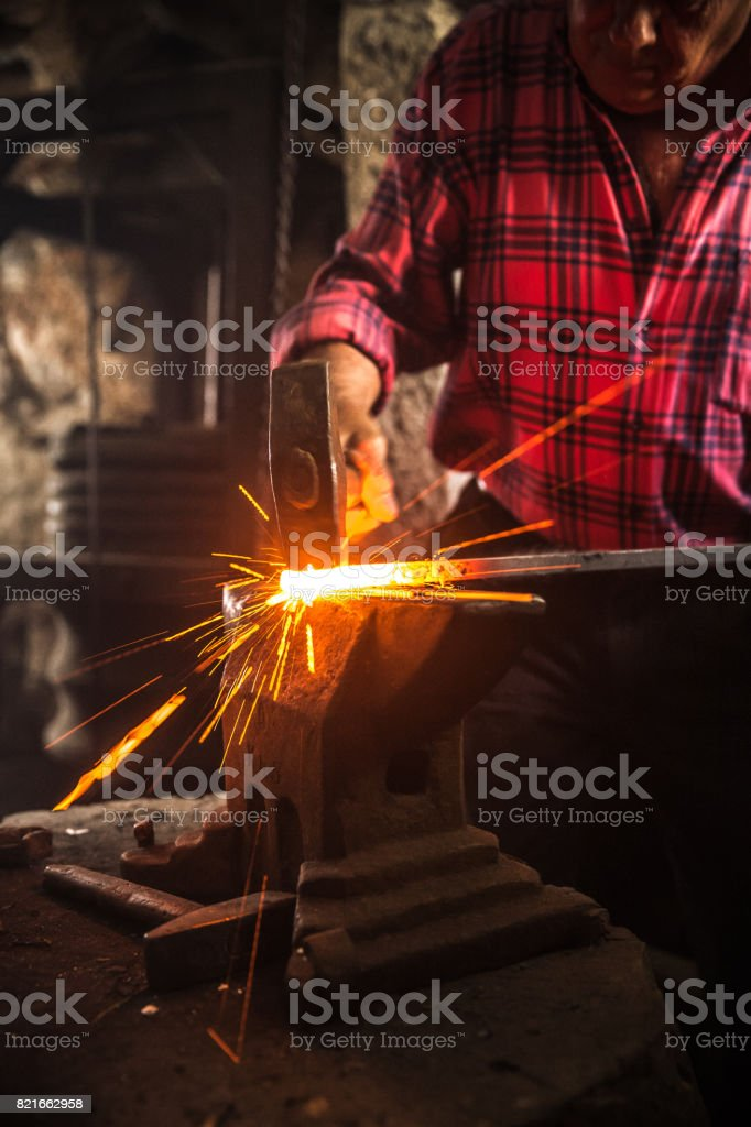 Senior Blacksmith Man Forging an Iron Craft on Anvil stock photo