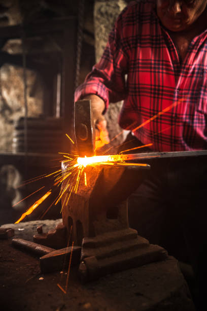 Senior Blacksmith Man Forging an Iron Craft on Anvil Senior Blacksmith Man Forging an Iron Craft on Anvil anvil stock pictures, royalty-free photos & images