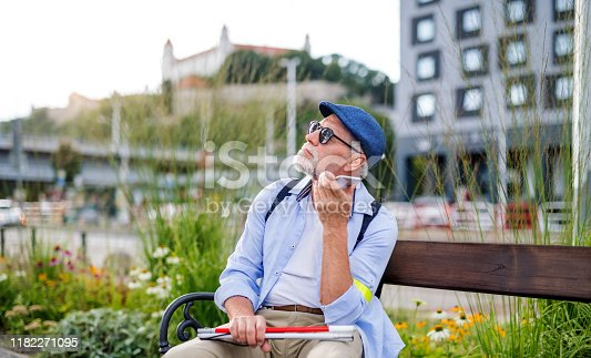 A senior blind man with smartphone sitting on bench in park in city, making phone call.