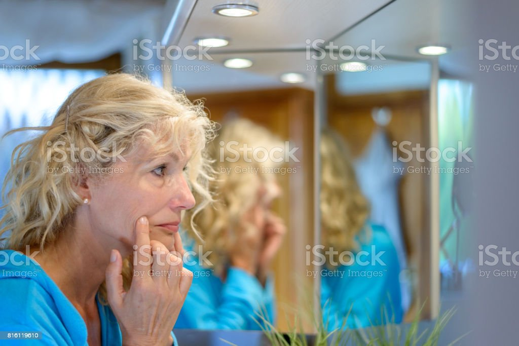 Senior blond woman checking her ageing skin stock photo