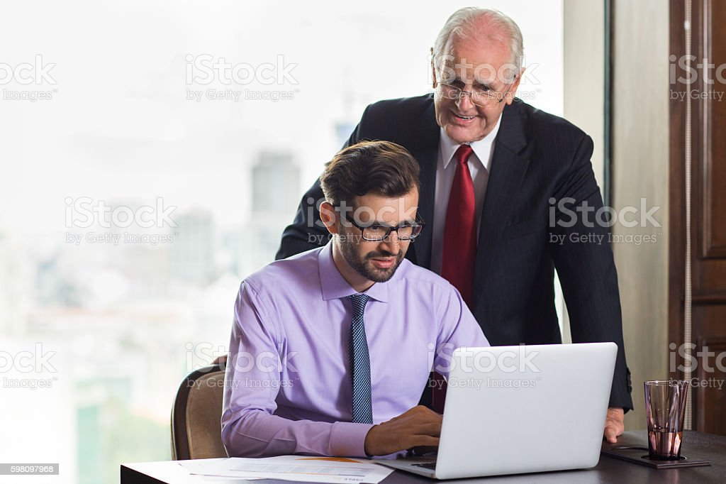 Senior boss consulting young subordinate working at laptop stock photo