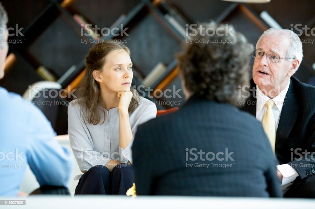 Senior Boss Explaining Ideas to Colleagues stock photo