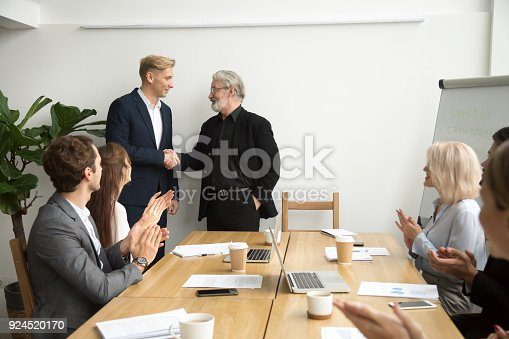 istock Senior boss promoting employee shaking hands team applauding at meeting 924520170