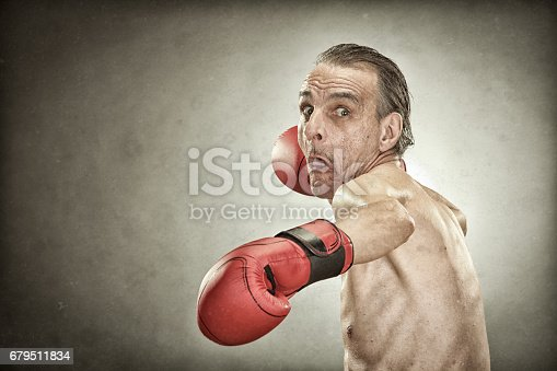 istock senior boxer man with red gloves old portrait on textured background 679511834