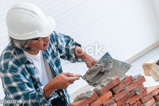 Senior builder is using cement on laying brick wall for construction concept.