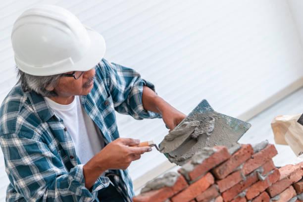 El constructor senior está utilizando cemento en la colocación de la pared de ladrillo para el concepto de construcción. - foto de stock