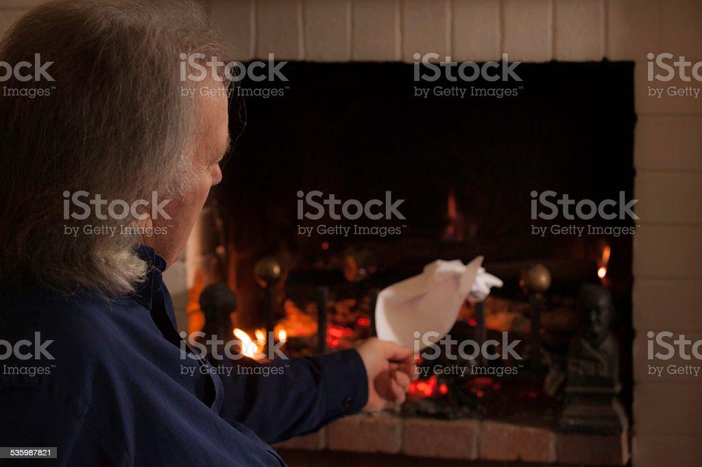 Senior burning paper in log fire stock photo