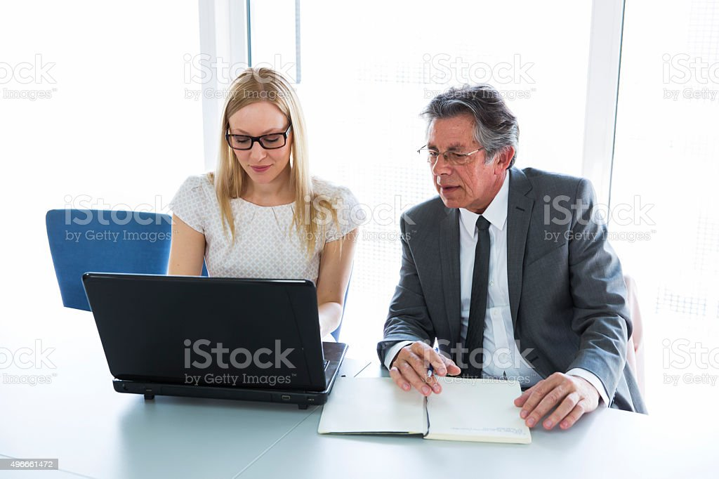 Senior business man and cute woman talking,working with laptop stock photo
