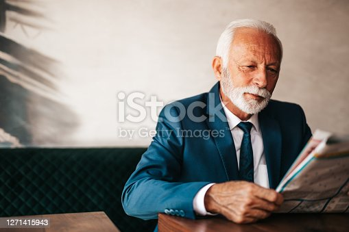 Handsome and elegant senior businessman sitting at restaurant table, reading newspapers and enjoying in fresh espresso coffee drink.