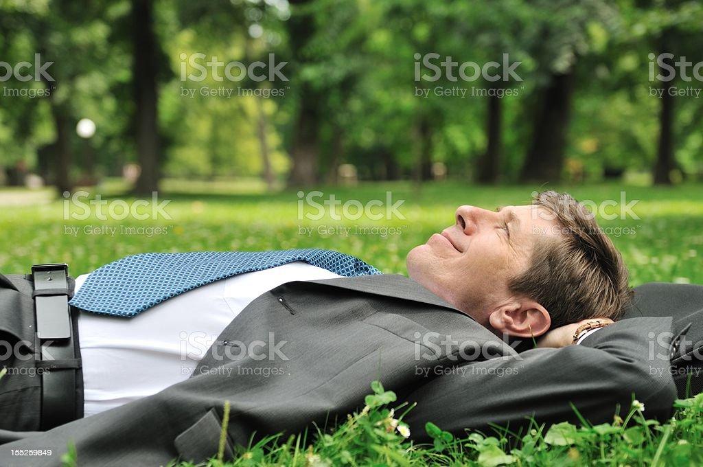 Senior business man lying in grass royalty-free stock photo