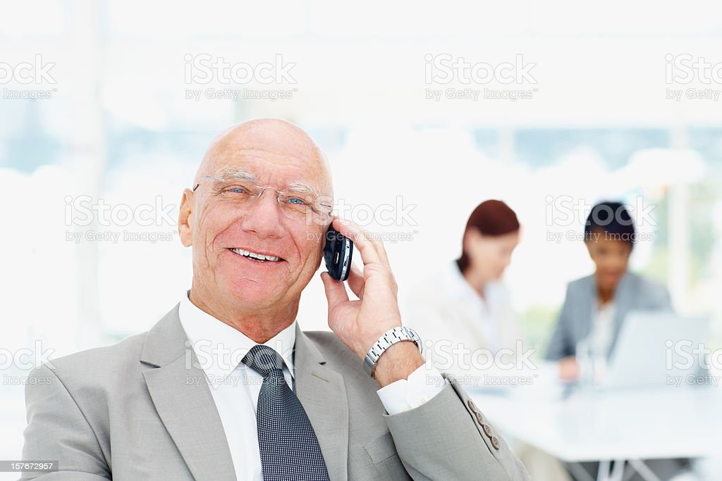 Senior business man talking on cellphone and team in background royalty-free stock photo