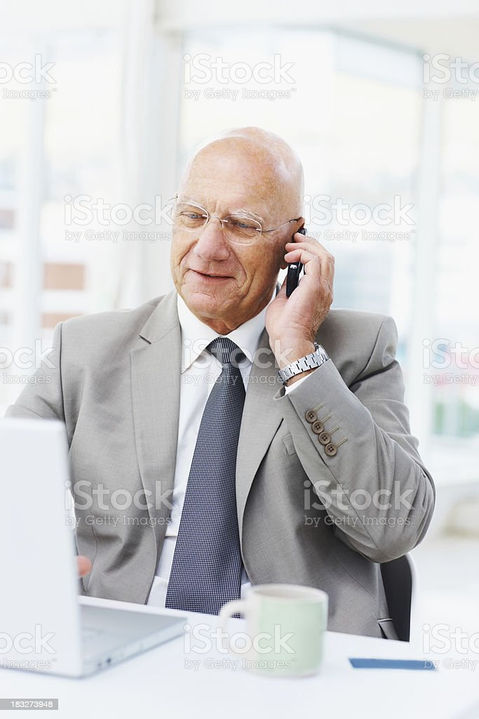 Senior business man talking over the cellphone while using laptop royalty-free stock photo