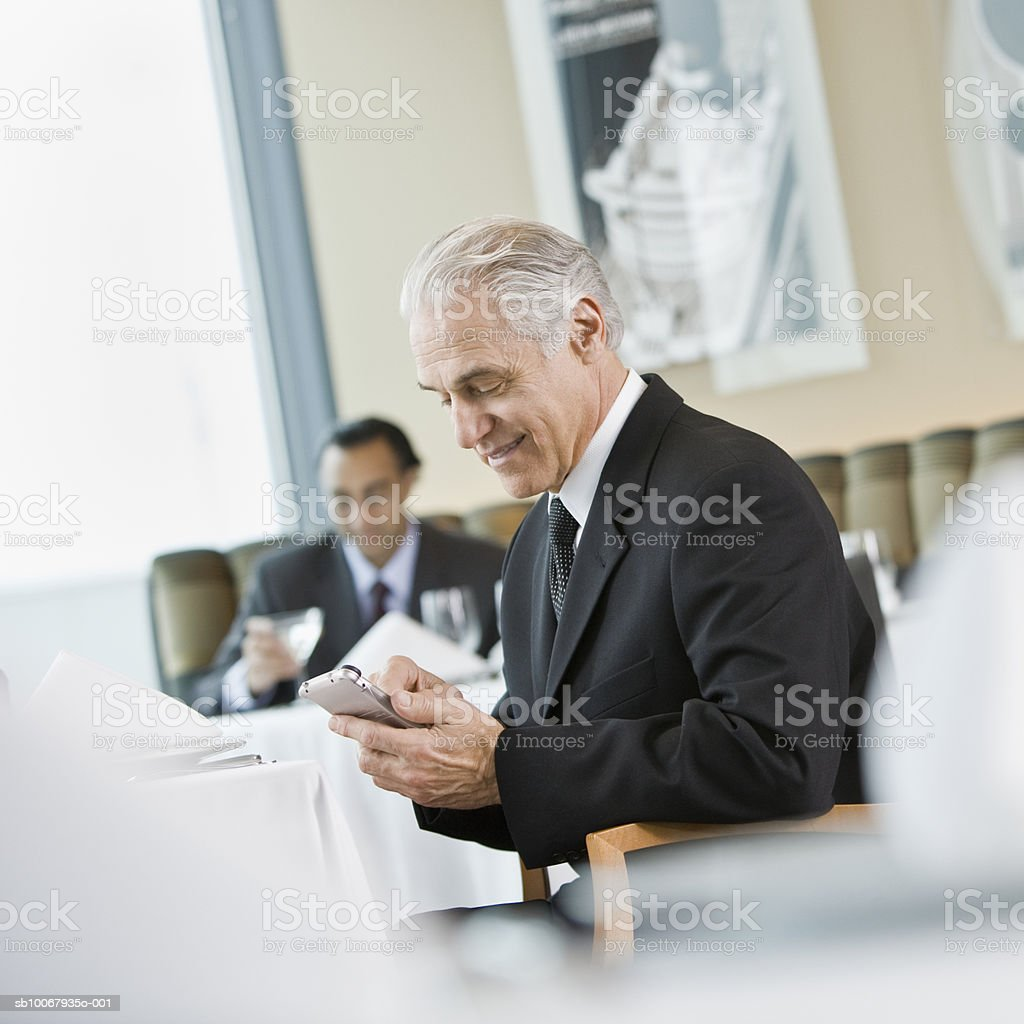 Senior business man using PAD in restaurant foto de stock libre de derechos