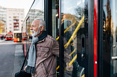 Mature Businessman get out a City Bus on a Cold Winter Day