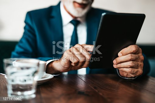 Handsome and elegant senior businessman sitting at restaurant table, reading news on electronic tablet and enjoying in fresh espresso coffee drink.