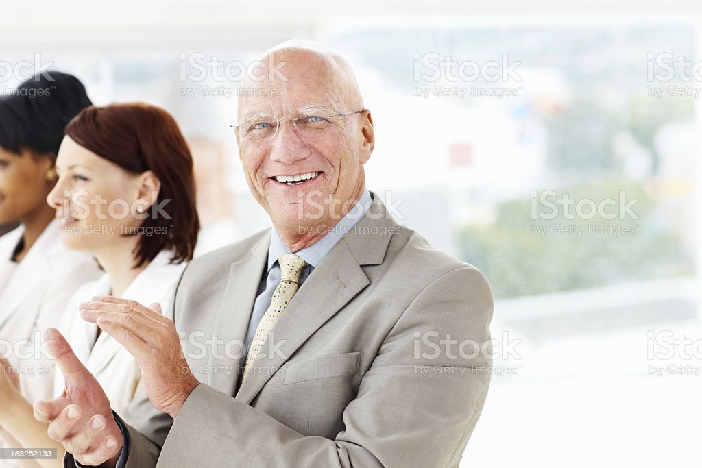 Senior business man with team clapping for a good presentation royalty-free stock photo