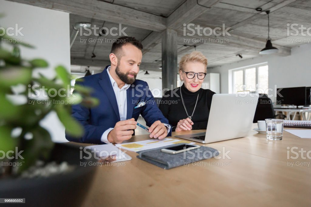 Senior business management team working together Mature businessman with senior businesswoman working on laptop computer in office Active Seniors Stock Photo
