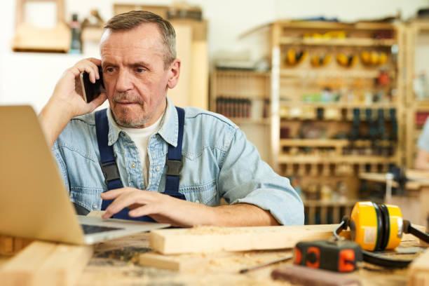 senior business owner - owner laptop smartphone foto e immagini stock