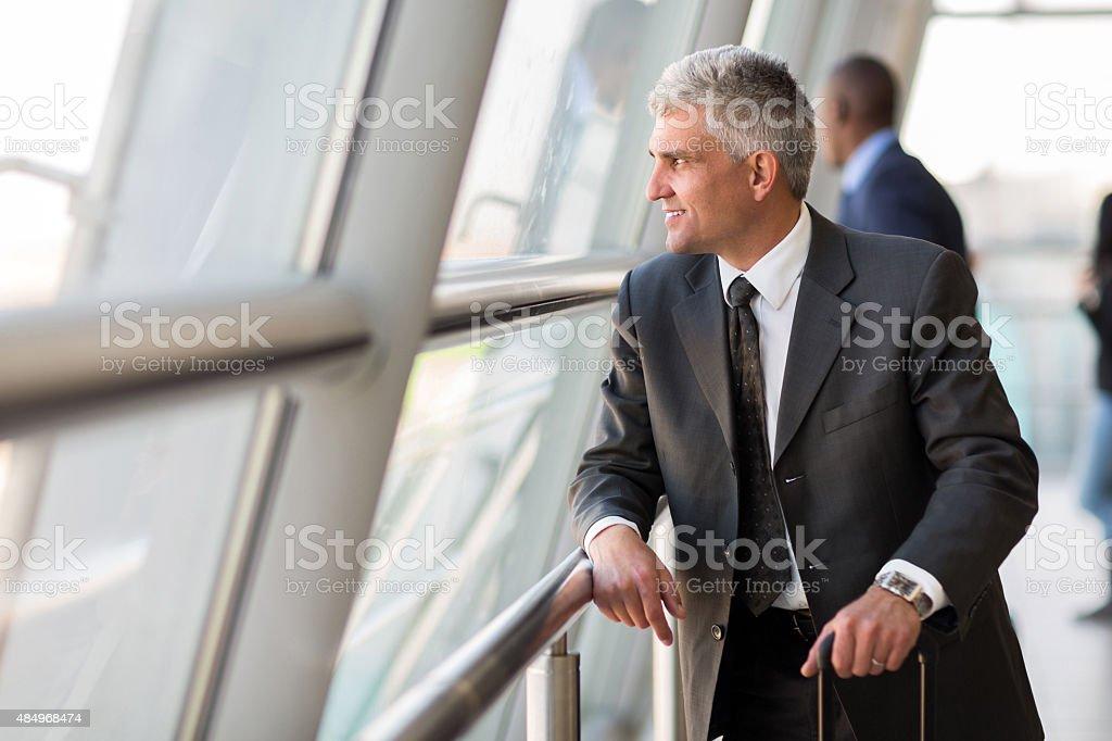 senior business traveler at airport stock photo