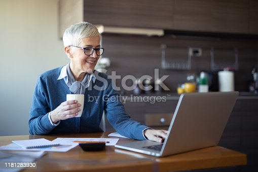 Female senior business woman using laptop at home office. Mature gray hair manager using computer while drinking coffee