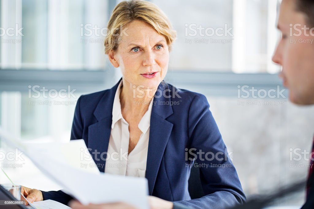 Senior business woman discussing new project with colleague Shot of senior business woman discussing new project with colleague during a meeting Women Stock Photo