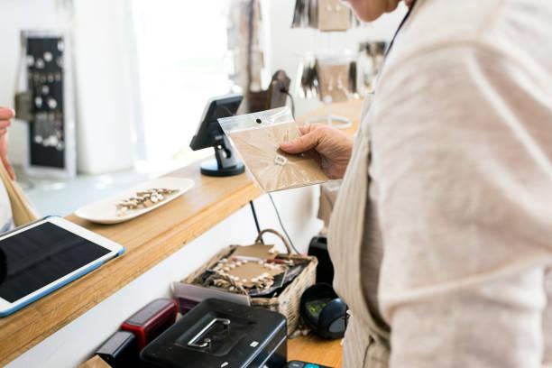 senior business-frau produkt an kunden übergeben - porzellan schmuck stock-fotos und bilder