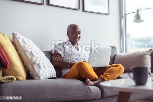 A black senior woman sits comfortably on her couch in her apartment. She is using a laptop and is consulting from home during the COVID-19 pandemic.