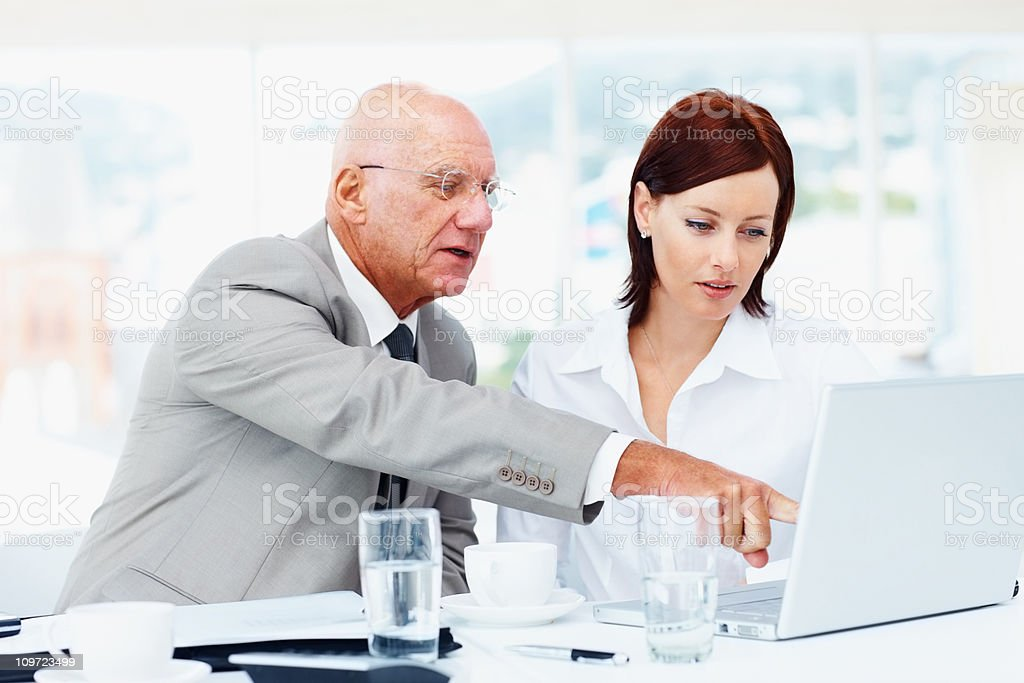 Senior businessman and business woman working on laptop royalty-free stock photo