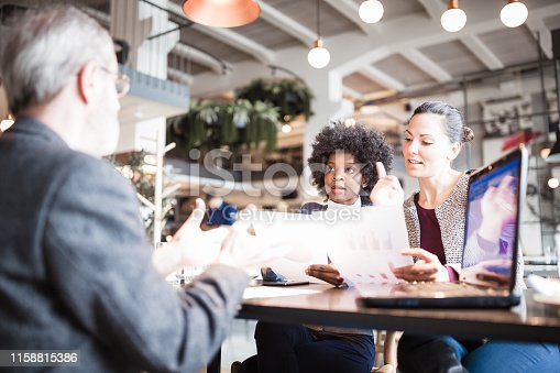 Senior businessman and his two female colleagues having business meeting in high end restaurant. Multi-ethnic group