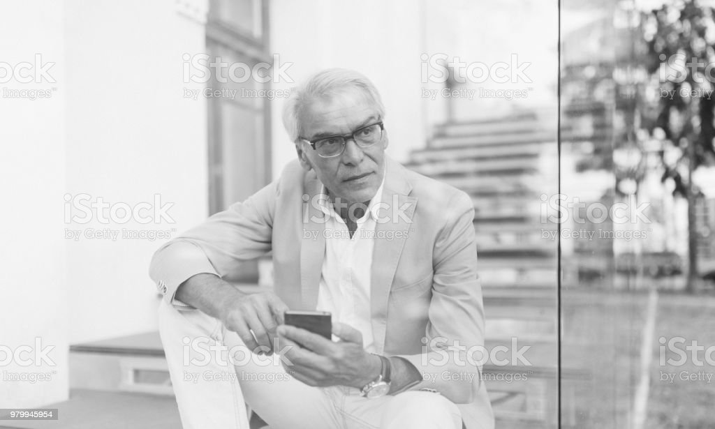 Businessman outside using phone and looking away