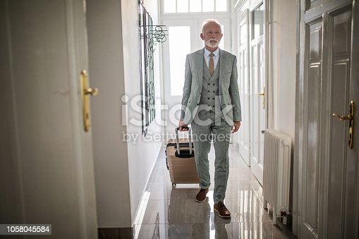 Fashionable senior businessman in suit, entering his hotel apartment packet with a suitcase.