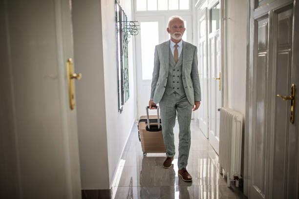 leitenden geschäftsmann in seinem hotelapartment - seniorenwohnungen stock-fotos und bilder