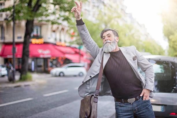homme d'affaires aîné saluant le taxi sur la rue - homme faire coucou voiture photos et images de collection