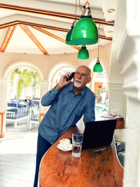 Senior businessman holding mobile phone while working on laptop Senior man holding smartphone and using laptop at bar counter old man working in a pub stock pictures, royalty-free photos & images