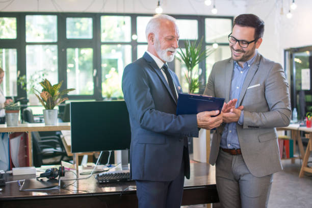 Senior businessman in formal wear discussing data from clipboard with younger male colleague while standing together in office. stock photo