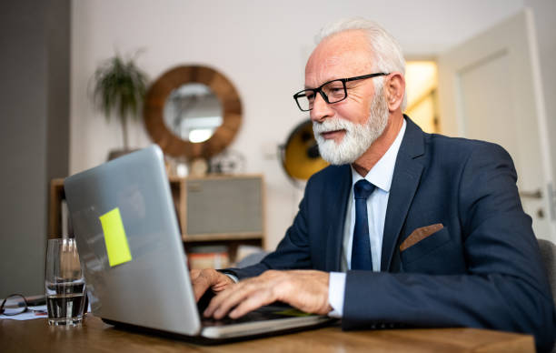 A senior businessman in his home, using his laptop. stock photo